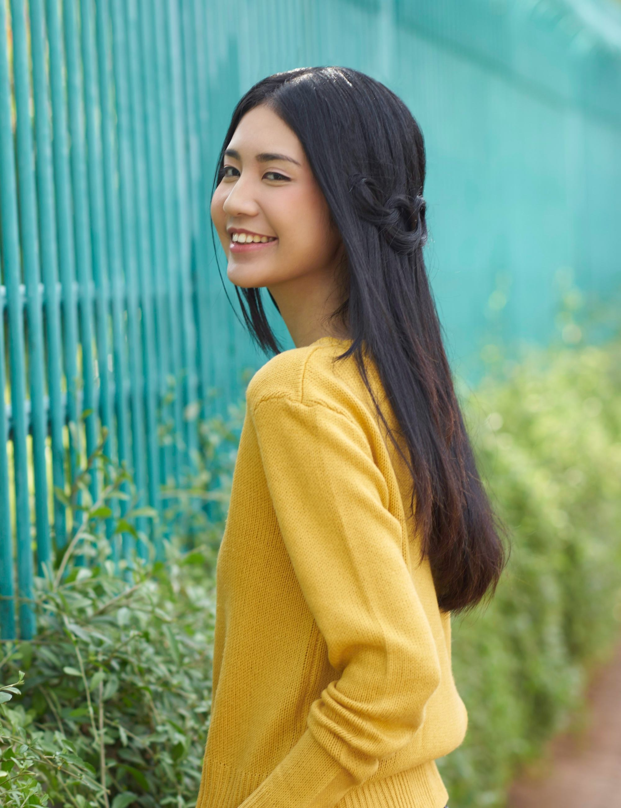 Asian woman with long black hair in a loop braid wearing a yellow sweater outdoors