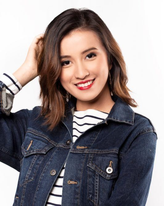 Messy layered bob: Asian woman scrunching her short dark brown hair wearing a denim jacket
