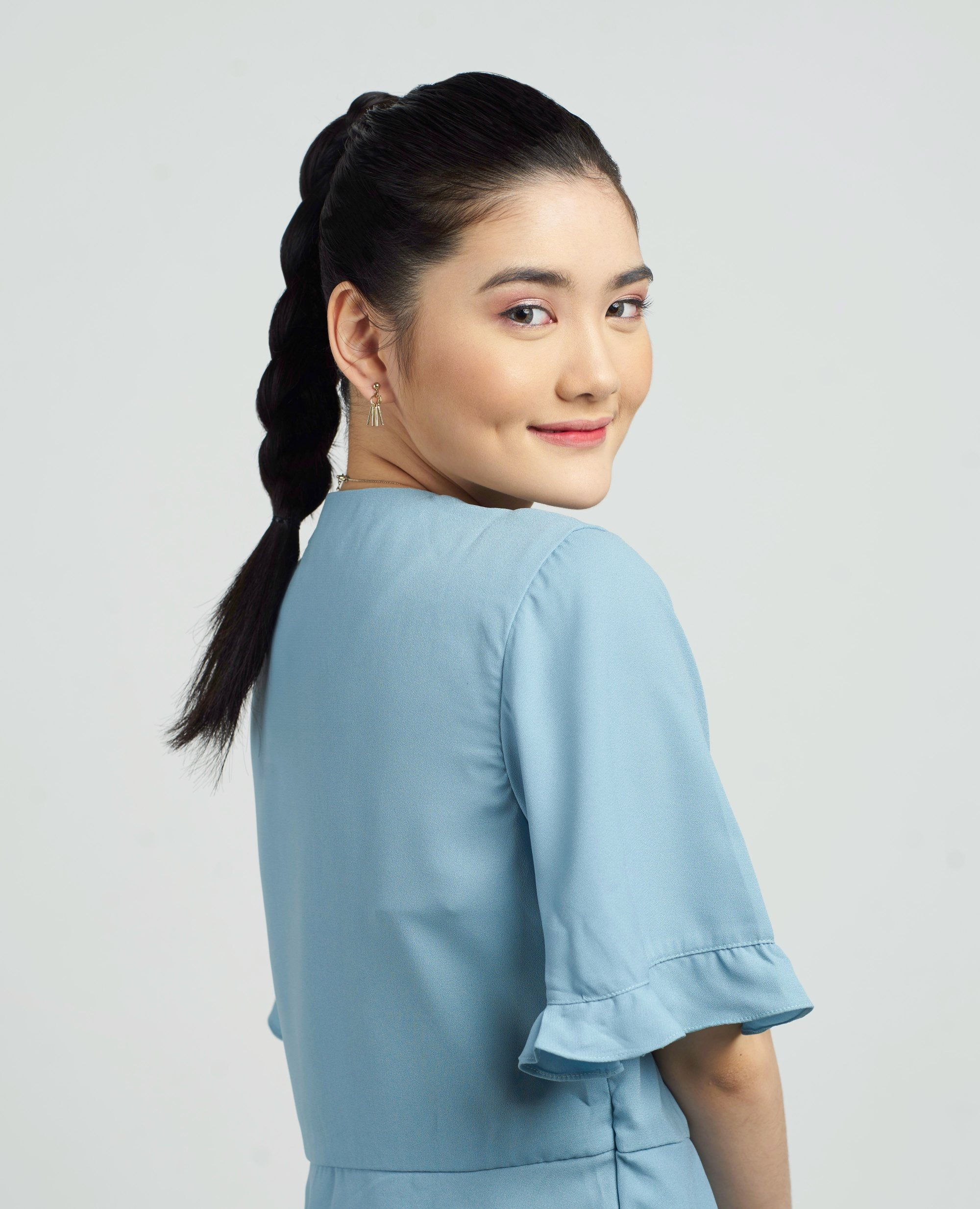 Summer braids: Asian woman with long black hair in a braid ponytail wearing a blue blouse