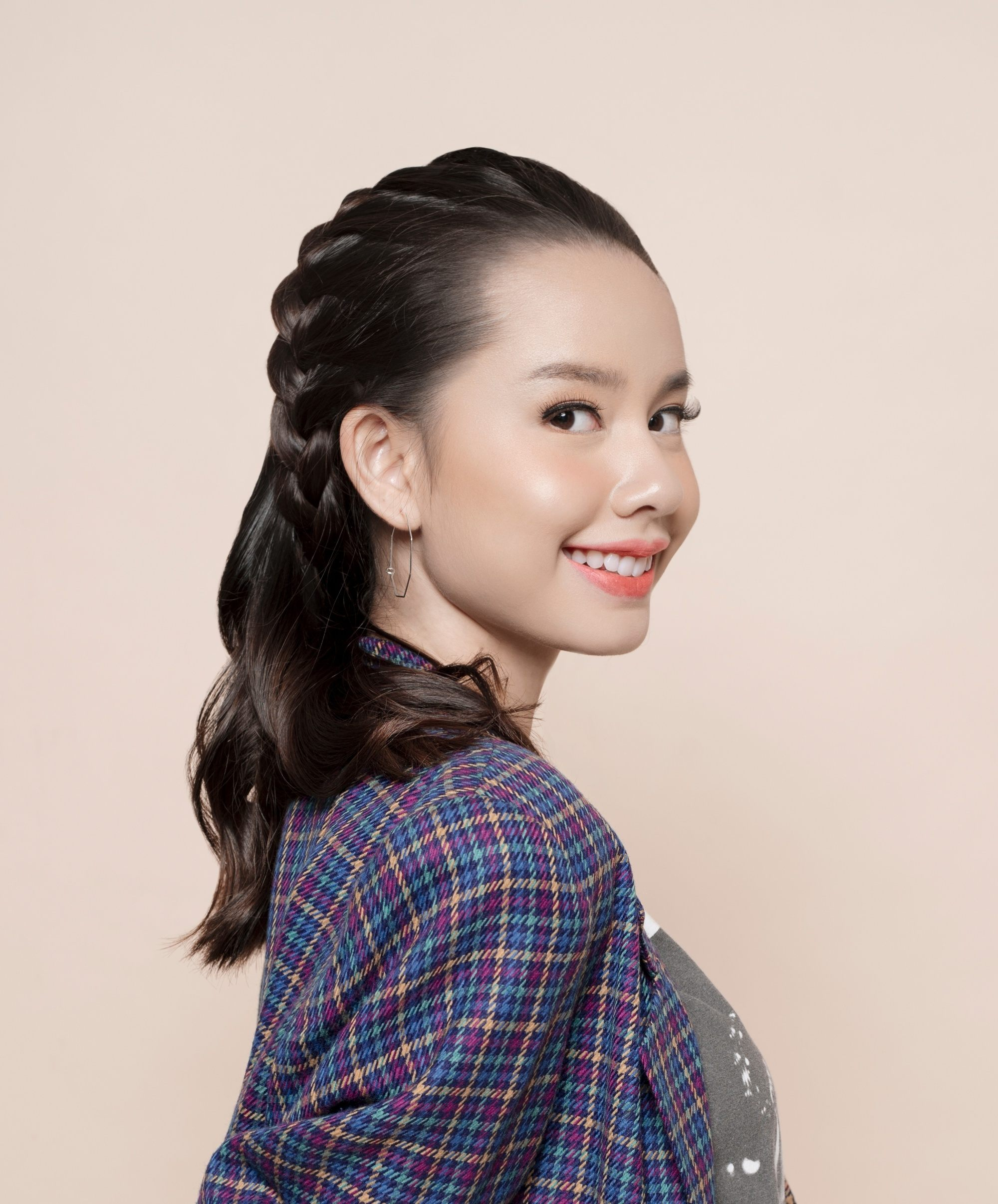 Summer braids: Asian woman with shoulder-length dark hair in a headband braid wearing a checkered polo and smiling