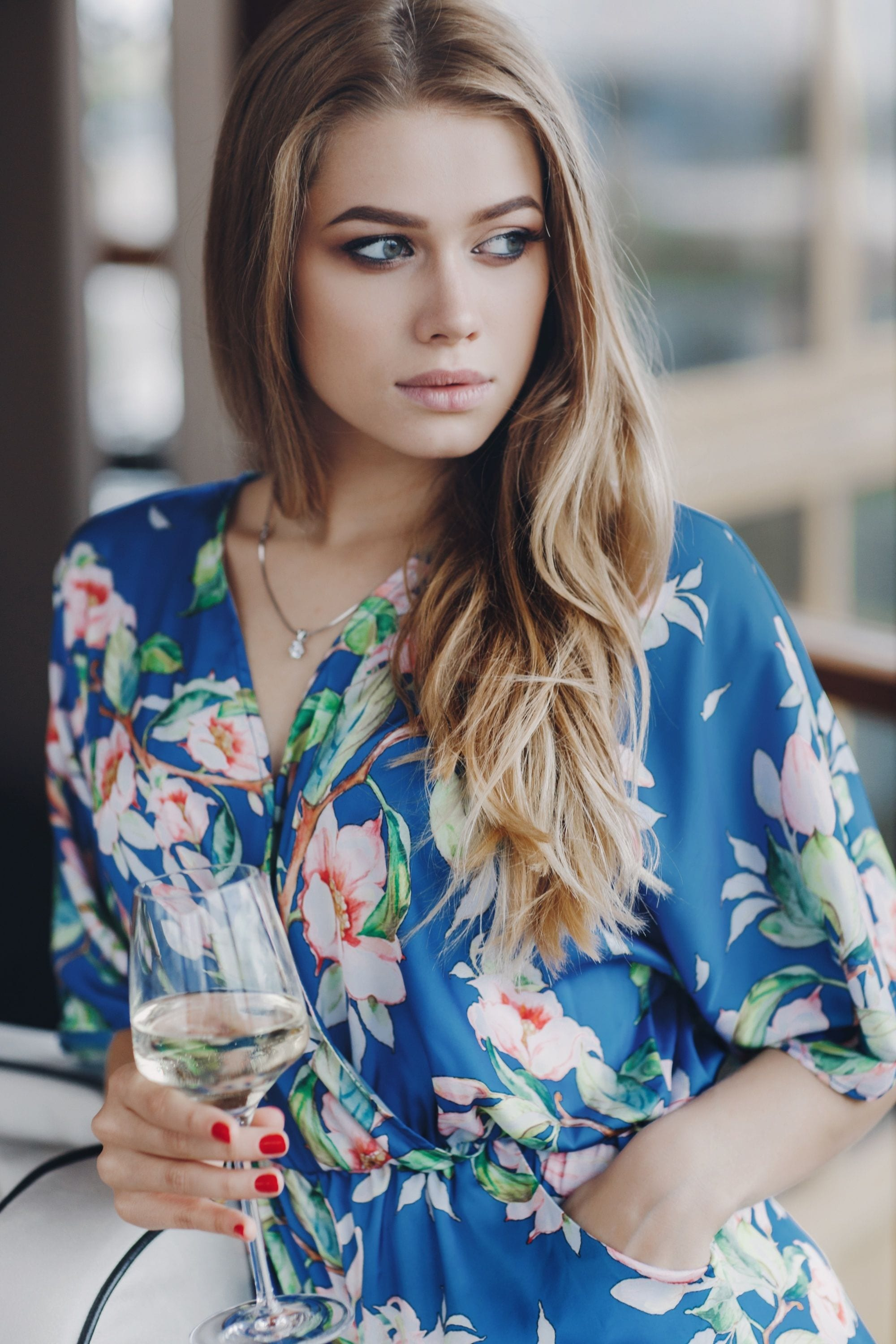 Ash hair color: Woman with long ash bronde hair wearing a blue floral dress