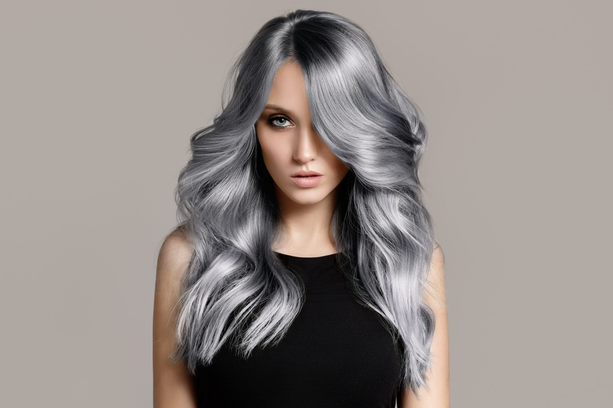 Ash hair color: Woman with long silver ash wavy hair wearing a black top