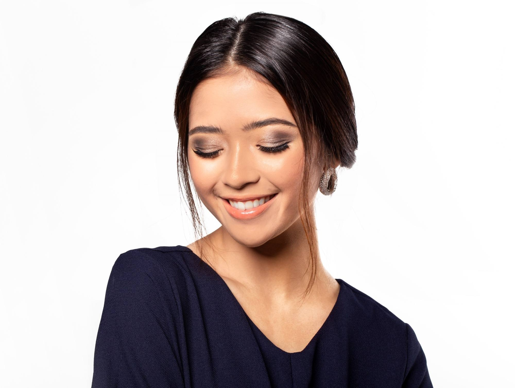 Chignon for short hair: Closeup shot of an Asian woman with dark hair in chignon smiling