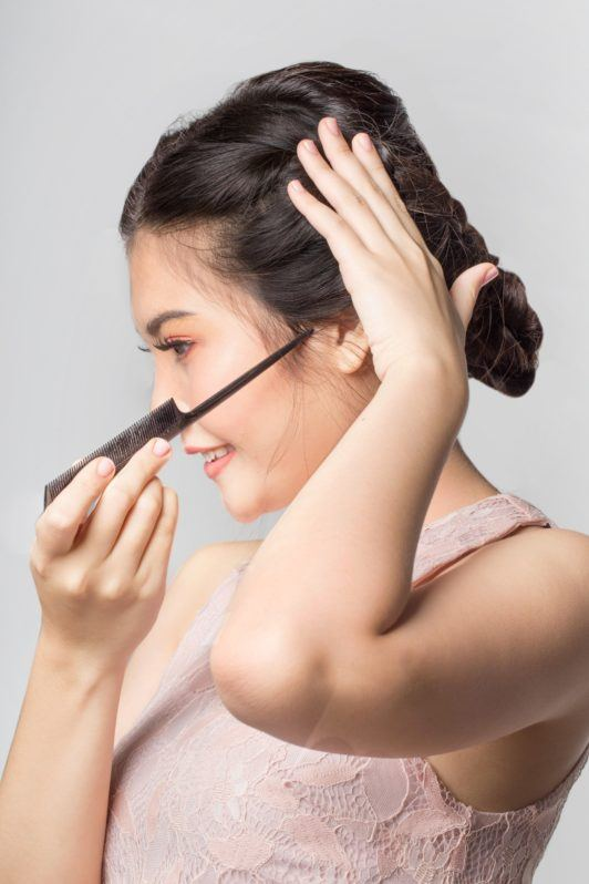 Lace braid updo: Side view of an Asian woman styling her hair