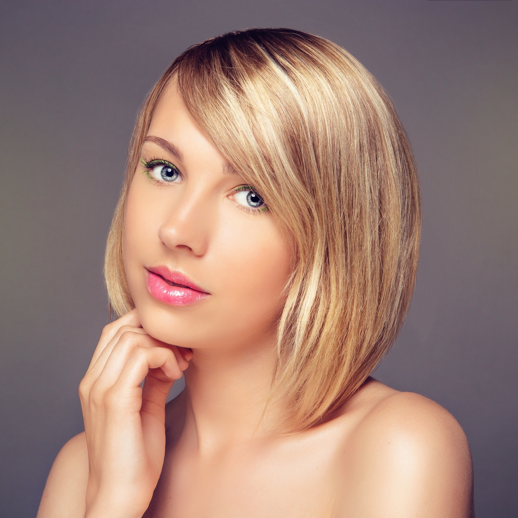 Long bob with bangs: Woman with blonde lob with side bangs against a gray backdrop