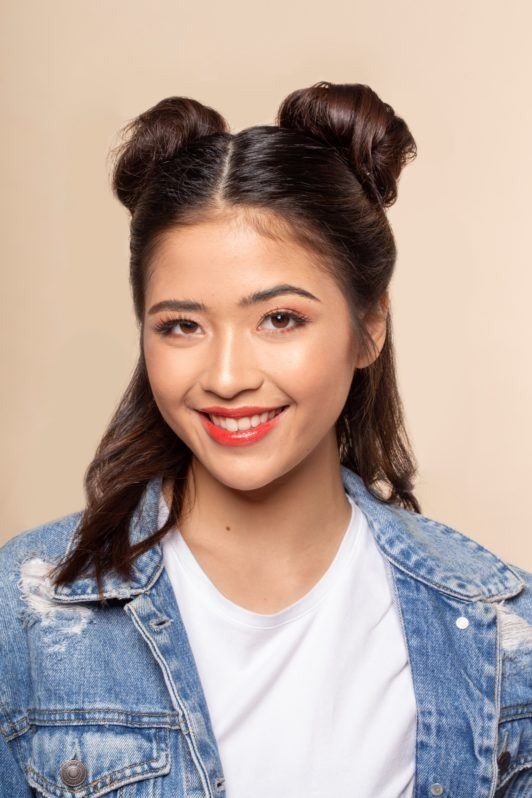 Space buns for short hair: Asian woman with half up bun hairstyle smiling
