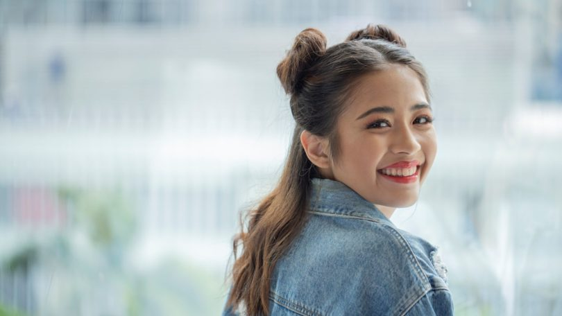 Space buns for short hair: Asian woman with shoulder-length dark hair smiling