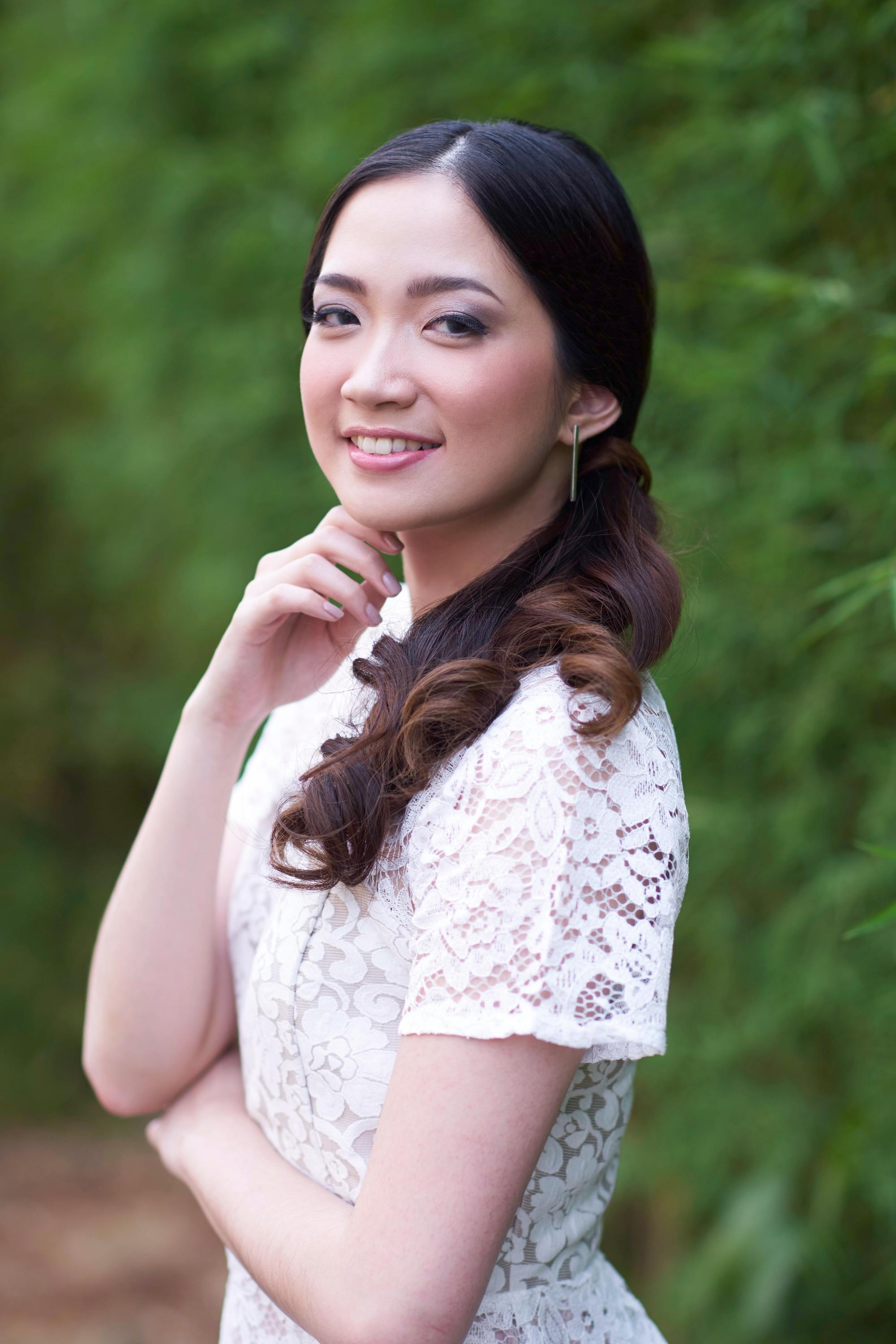 Graduation Hairstyles: Asian woman with long dark hair in curly side ponytail