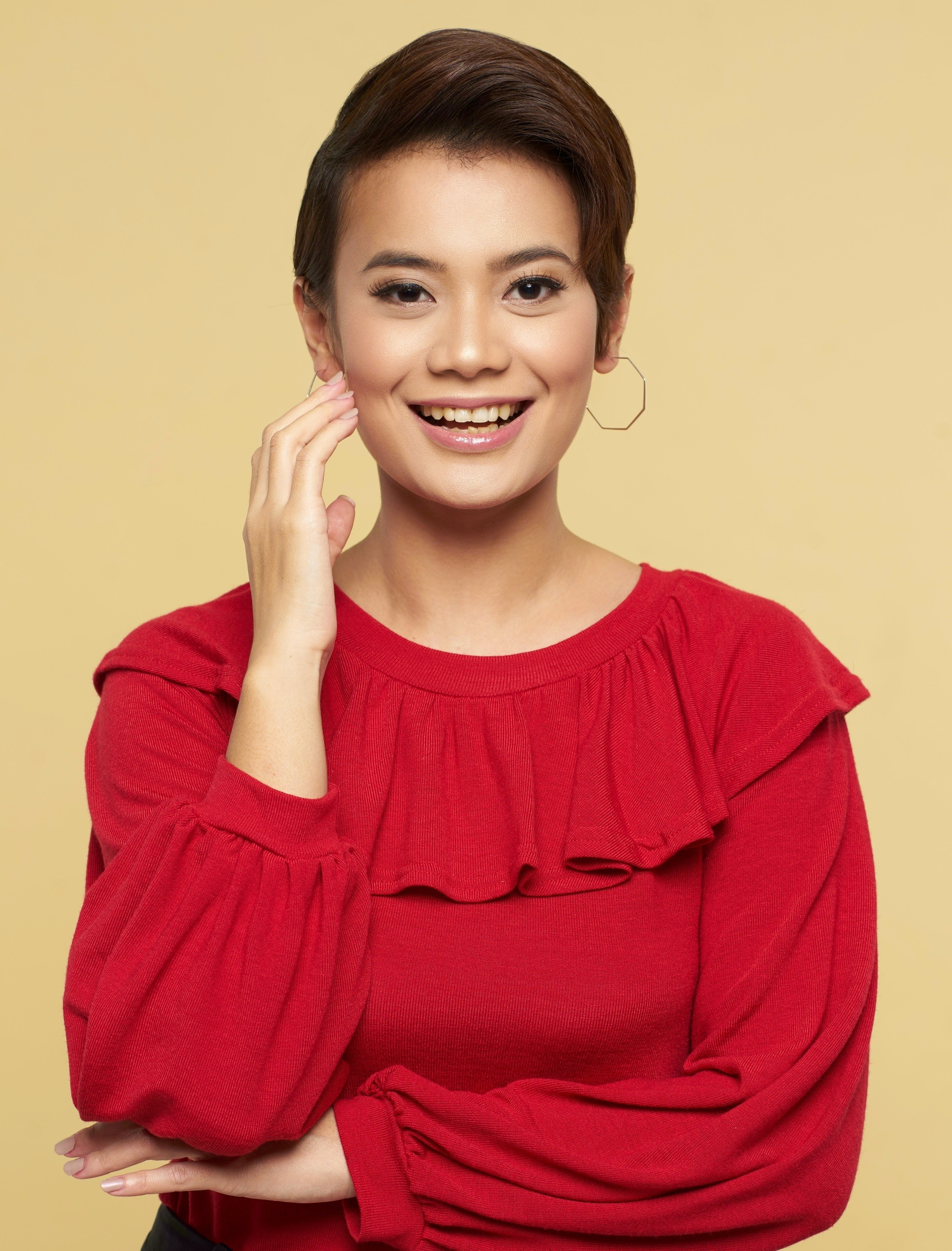 Graduation hairstyles: Asian woman with pixie cut wearing a red blouse smiling