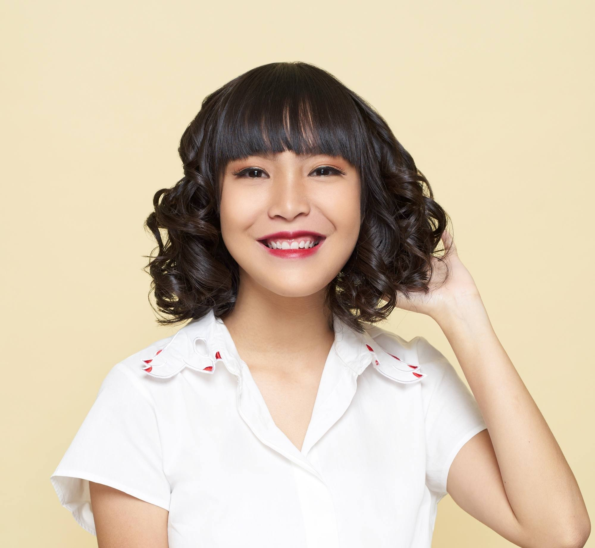 Layered curly hair: Asian woman with short black curly hair smiling