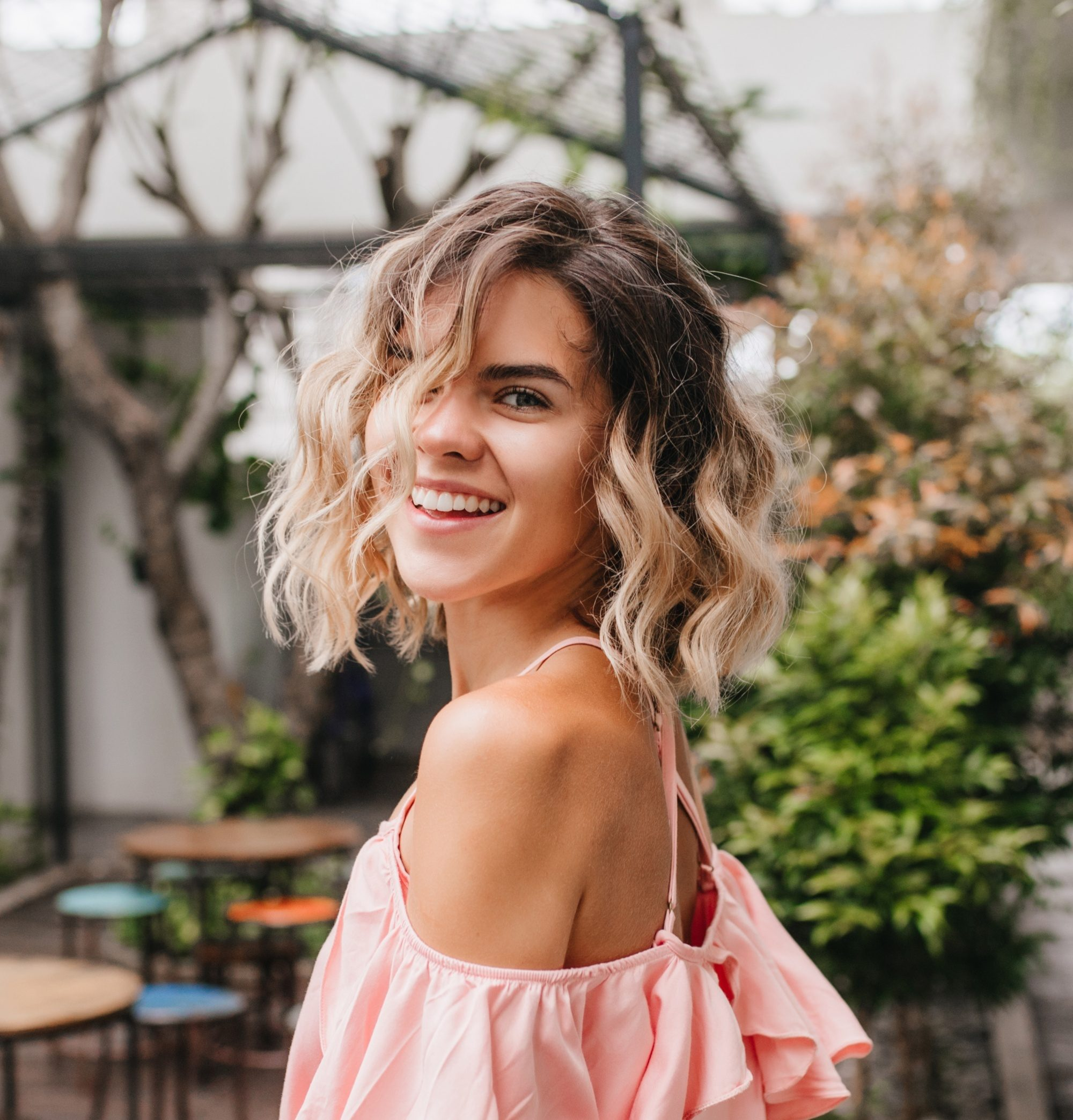 Layered curly hair: Woman with short ombre curly hair smiling