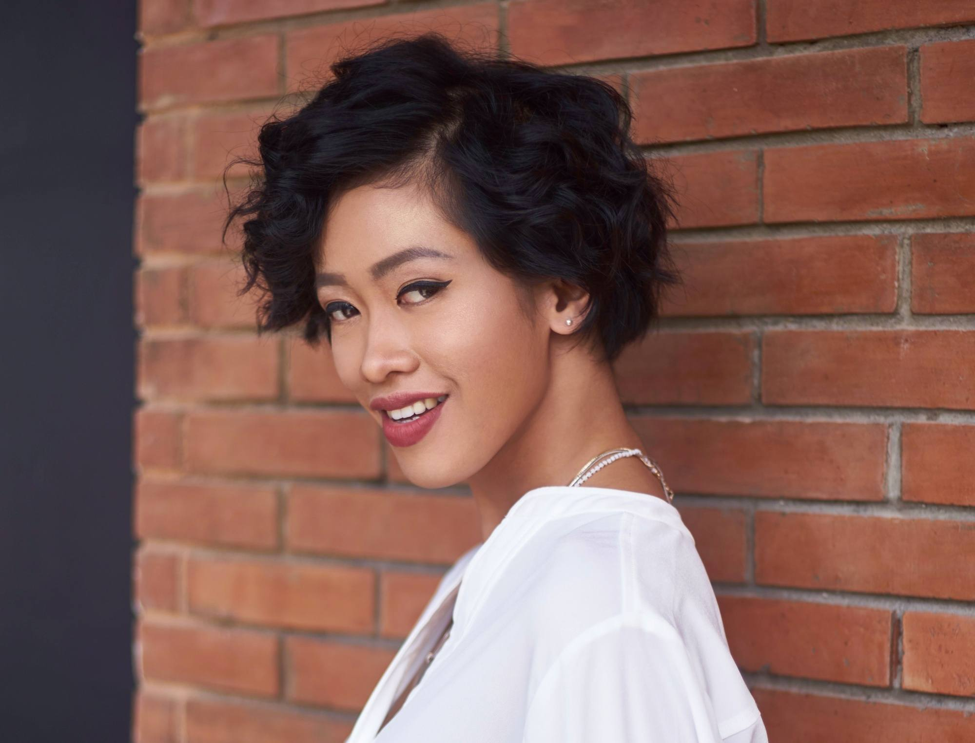 Layered curly hair: Closeup shot of an Asian woman with short black curly hair