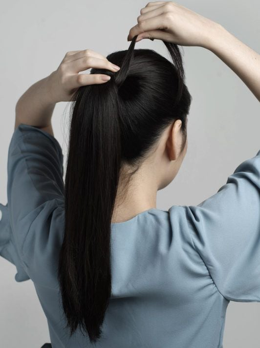 ผู้หญิงผมยาวสีดำ ถักเปียหางม้า สวมเสื้อสีฟ้า